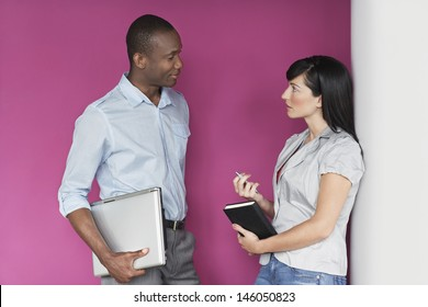 Casual multiethnic young male and female executives talking against pink wall