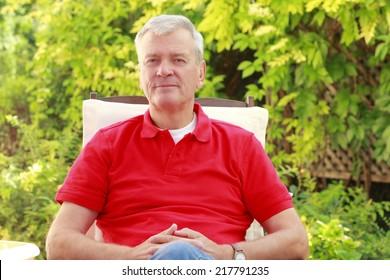 Casual old man sitting at nursing home garden.