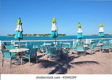 Casual Outdoor Waterfront Dining Area With Island In Background