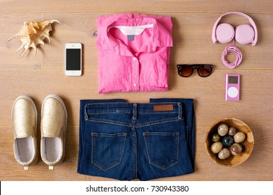 Casual outfit laid out on a wooden background. Shoes, jeans, pink shirt, sunglasses, phone, pink music player and headphones. Sea shell and a bowl of colored stones as sidepieces.