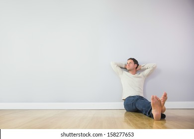 Casual pensive man leaning against wall with crossed arms in bright room