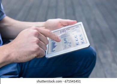Casual person using digital tablet computer to analyze a financial dashboard with charts and key performance indicators (KPI) for stock market investment and business intelligence (BI), closeup screen