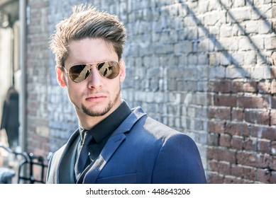 Casual portrait of a handsome young male model near a brick wall. Attractive man wearing sunglasses. Space for copy. Sunlight beams background.