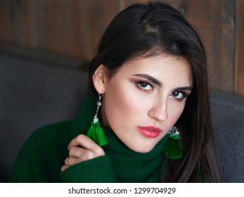 Casual portrait of happy young brunette woman with trendy makeup green sweater and brush earrings.