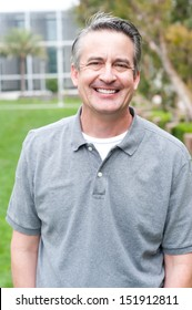 casual portrait of a mature, happy man taken outside