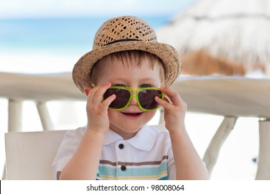 Casual portrait of a toddler boy in bright sunglasses