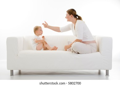 Casual portrait of a young mother and toddler sitting on a white couch facing each other and interacting.