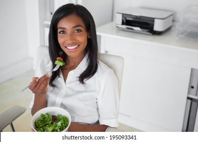 Casual pretty businesswoman eating a salad at her desk in her office