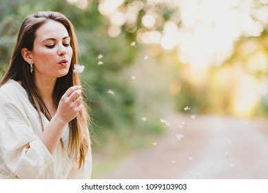 Casual pretty young girl blowing a flower and blowing dandelion seeds