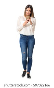 Casual pretty young woman typing on the smart phone. Full body length portrait isolated over white background.