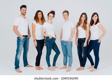 Casual relaxed barefoot group of young male and female friends in jeans and white tops standing in a line over a white background smiling at the camera