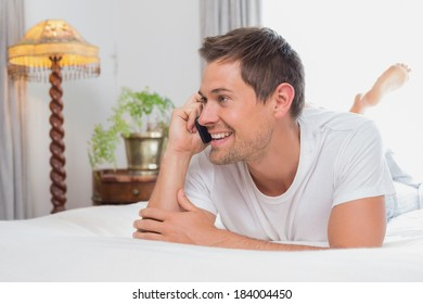 Casual relaxed young man using mobile phone in bed at home
