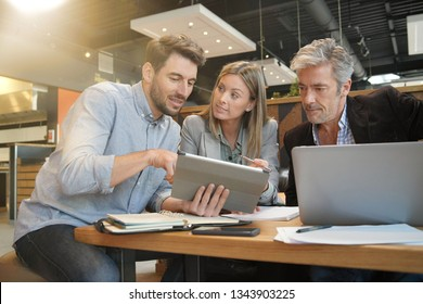 Casual sales team working through presentation with manager