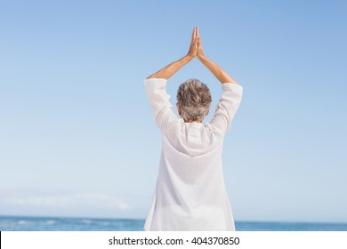 Casual senior woman with arms outstretched on a sunny day
