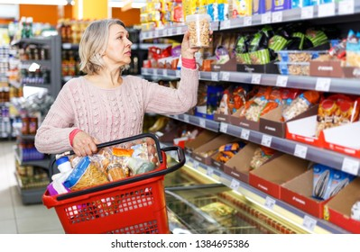 Casual senior woman doing shopping in grocery department of supermarket