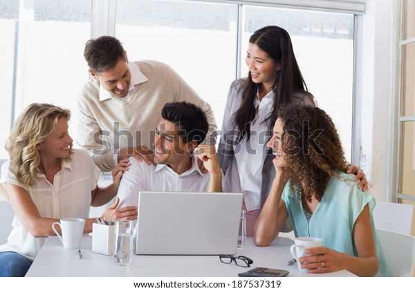 Casual smiling business team congratulating their colleague in the office