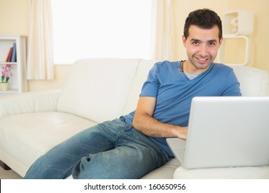 Casual smiling man sitting on couch using laptop looking at camera in bright living room