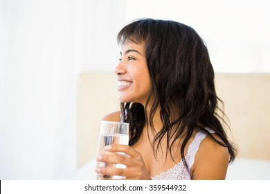 Casual smiling woman holding a glass of water at home