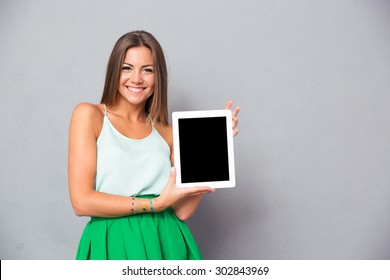 Casual smiling woman showing blank tablet computer screen over gray background. Looking at camera