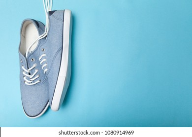 Casual sneakers on blue background, copy space for text.
