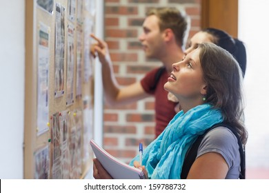Casual students looking at notice board in college