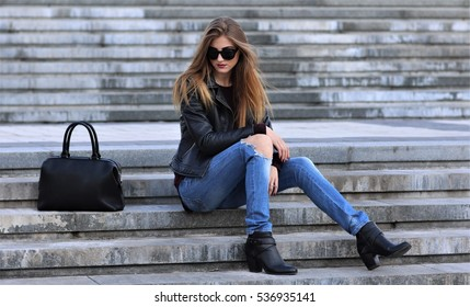 Casual style. Stylish woman in sunglasses sitting on the stone stairs. She dressed in leather jacket, skinny jeans and shoes on heels. Her sight directed downwards. Long hair, elegant, street fashion