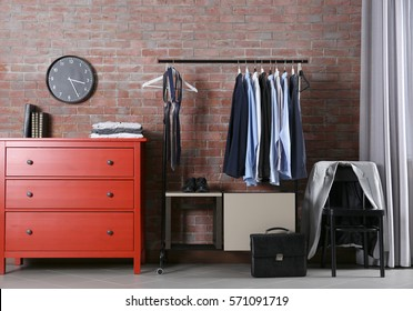Casual stylish male clothes on hanger stand in room