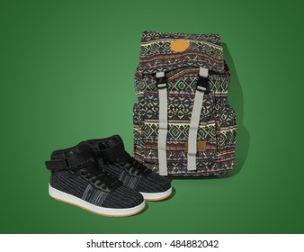 Casual trendy flat hi-cut pair of shoes and patterned bag on green background