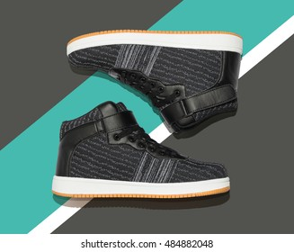 Casual trendy flat hi-cut pair of shoes on abstract background