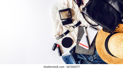 Casual  trendy outfit of young stylish woman. Essentials for modern   lady. Jeans jacket , note book,  white dress ,lipstick,powder, pen, leather bag, straw hat, perfume .