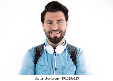Casual wear content young man posing with backpack and headphones. Student and education concept isolated on white background.