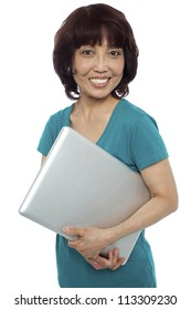 Casual woman carrying her laptop and smiling at camera