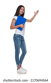 casual woman holding blue clipboard presents to side while standing on white background, full length picture