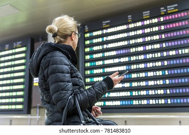 Casual woman in international airport looking at the flight information board, checking her flight.
