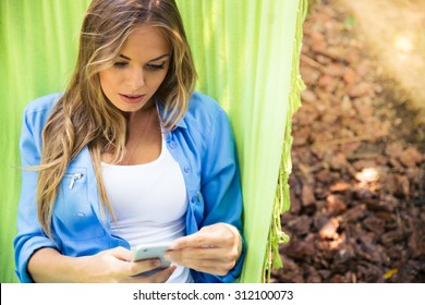 Casual woman lying on hammock and using smartphone outdoors