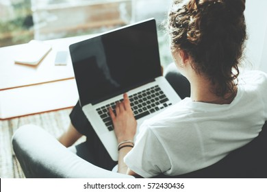 Casual woman manager sitting in her office workspace with computer and big bright window