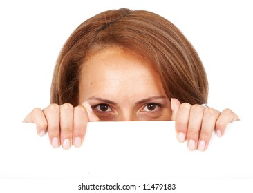 casual woman peeping over billboard sign isolated over a white background