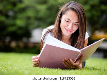 Casual woman studying outdoors laying on the grass