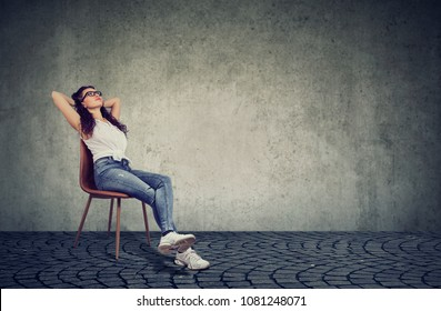 Casual woman taking rest on chair dreaming of vacation and holding hands behind head.