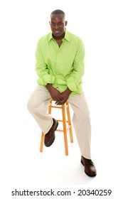 Casual young African American man standing in a bright green shirt sitting comfortably on a stool.