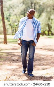 casual young african american man walking in the park and looking away