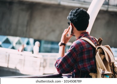 Casual Young asian man with backpack talking on mobile phone in the city.