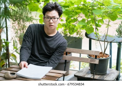 Casual young asian man wear glasses and reading magazine in front garden.