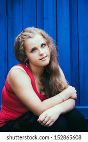 Casual Young Blue-Eyed Girl Sitting Near Blue Wooden Wall. Red T-shirt