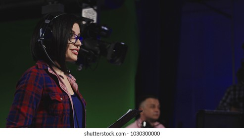 Casual young brunette in headset working in telecasting studio as stage director supervising footage making and cheerfully talking to colleagues.