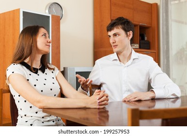 Casual young couple having serious talking at table in living room