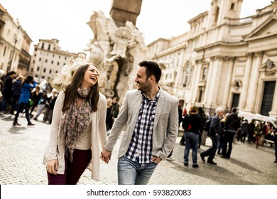 Casual young couple holding hands walking in Rome, Italy, Europe.