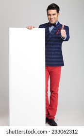 Casual young fashion man showing the thumbs up sign while presenting a white board.
