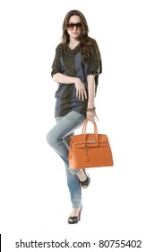 casual young fashion mode in sunglasses with handbag show in studio