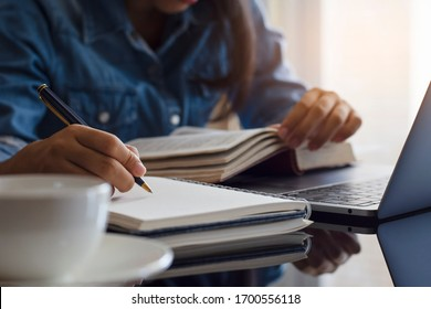 Casual young female student handwriting information on diary notebook while reading book and work on laptop computer with white cup of coffee on the table at home.